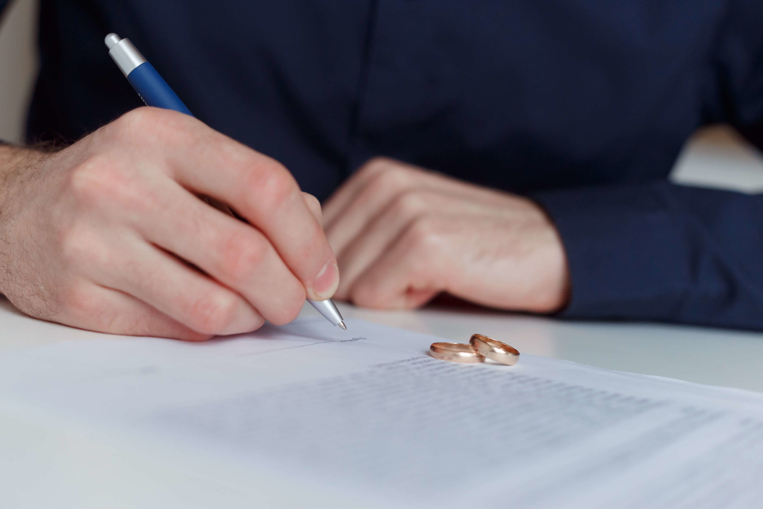 man alone filling in divorce papers with wedding rings on table